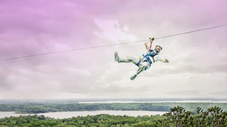 1920x1080 of man ziplining at Brainerd Zip Line Tour above the trees