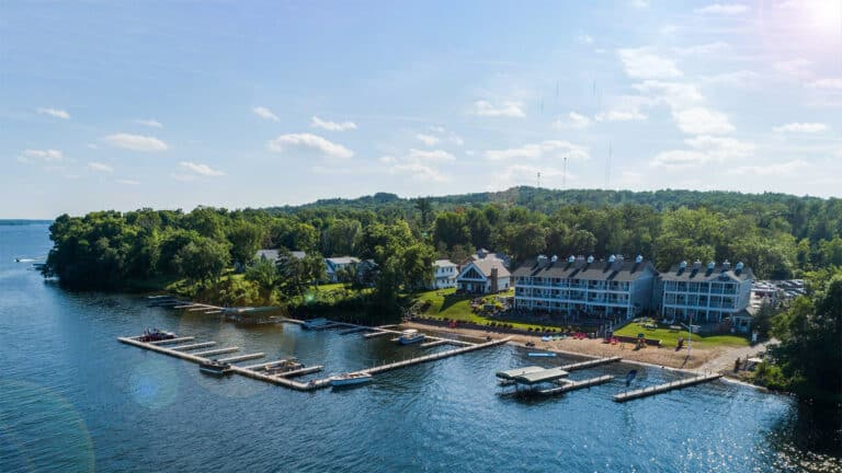 1920x1080 aerial photo of Quarterdeck Resort showing the large three story lodging building along the lakeshore, with a sandy beach and boat docks, and Gull Lake in the foreground and Forest in the Background on a warm sunny summer day