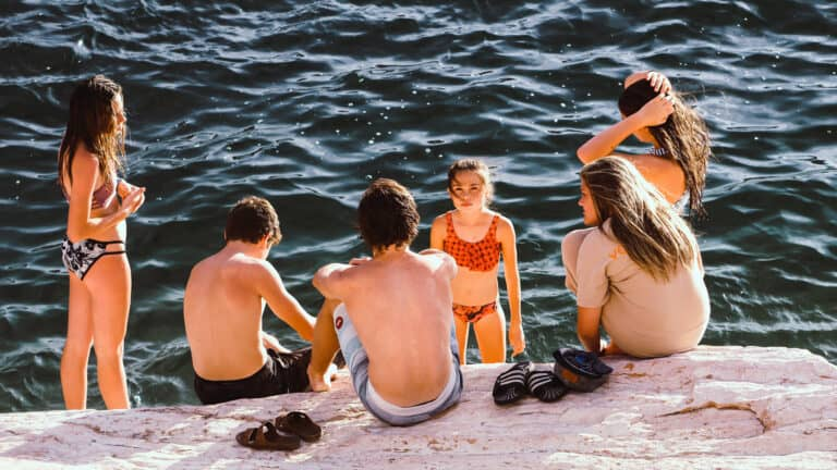 1920x1080 photo of a group of kids sitting by the edge of a lake on a warm summer day