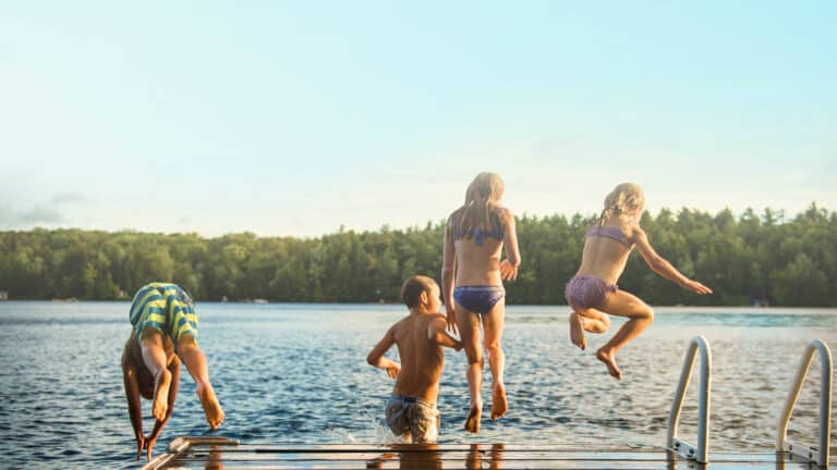 1920x1080 photo taken behind kids jumping off of dock into a lake on a warm summer day with the lake and pine trees in the background
